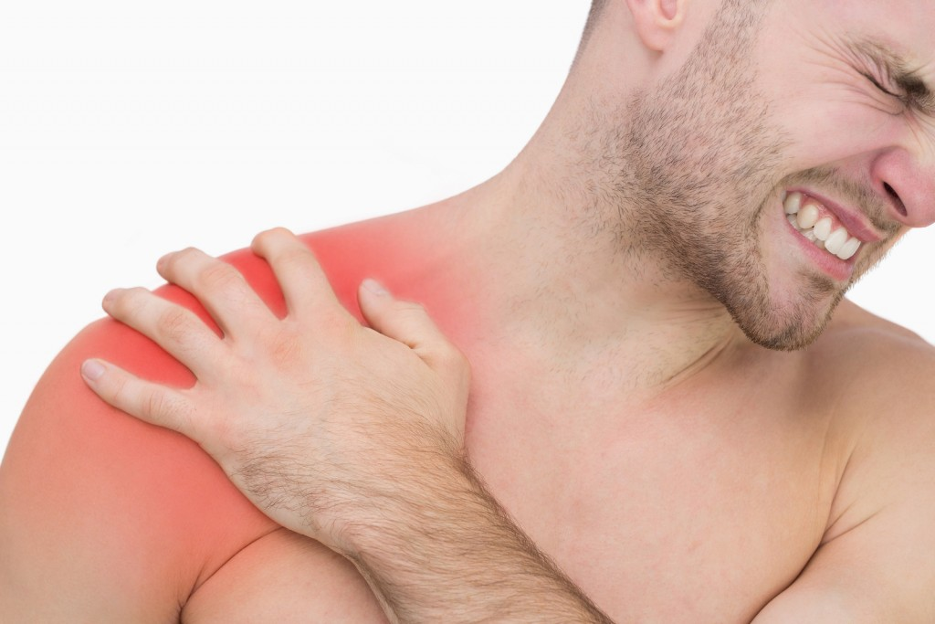 Closeup of young shirtless man with shoulder pain over white bac